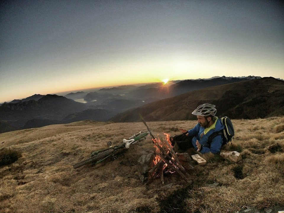 Cyclist and the campfire in the mountsins